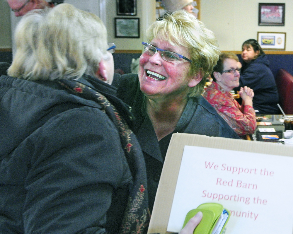 RAISING MONEY: REd Barn Owner Laura Benedict, right, hugs Carol Foreman, of South China, in November after she brought a sign supporting The Red Barn after the state attorney general notified the restaurant that it was violating state law. A bill heard Thursday would make it easier for small businesses to legally conduct fundraisers for charities.