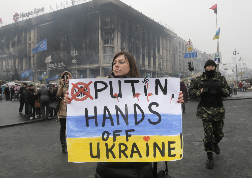 A woman holds a poster against war at Kiev's Independence Square, in Ukraine, Thursday, March 6, 2014. The Heads of State of the EU will meet Thursday in emergency session in Brussels to discuss the situation in Ukraine. The destroyed trade union offices which was burned in clashes seen in the background.