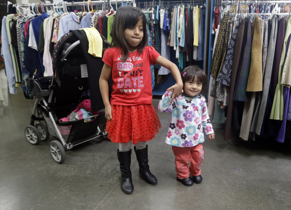 Two young girls hold hands as their mother sifts through used clothing at Sacred Heart Community Service recently in San Jose, Calif.