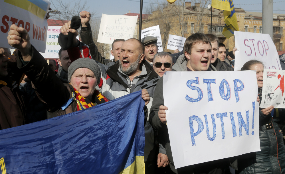 Demonstrators carry banners during a rally near the Russian embassy in Kiev, Ukraine, on Friday. As a result of its move into Ukraine, Russia already has lost billions from a stock market drop and the devaluation of the ruble.
