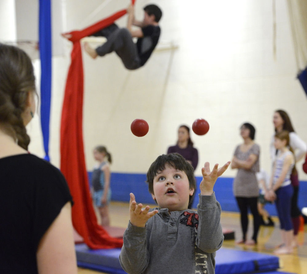Martha Fournier shows Kyle Brown, 8, of Gorham how to juggle. Above left, Kyle gets the hang of it.
