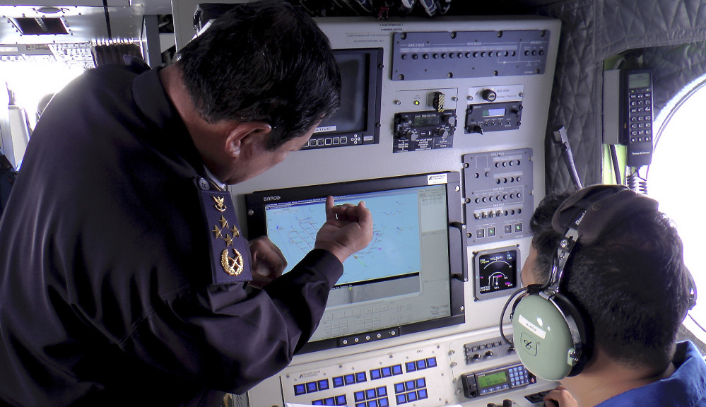 Adm. Mohd Amdan Kurish, left, of the Malaysian Maritime Enforcement Agency checks radar Sunday during a search for the missing Malaysia Airlines plane off Tok Bali Beach in Kelantan, Malaysia.