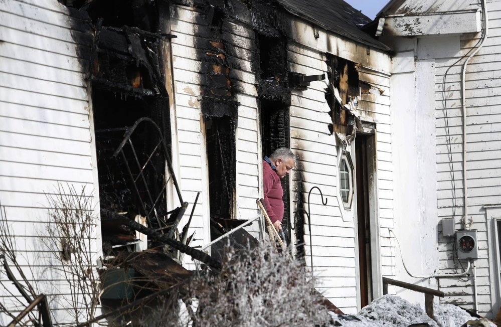 Fire investigator Dan Young leaves a Limington home Monday after taking photos in the aftermath of a fire that killed a woman earlier that morning. The fire was reported by a passer-by at 5:30 a.m., and firefighters arrived minutes later to find the house engulfed in flames.