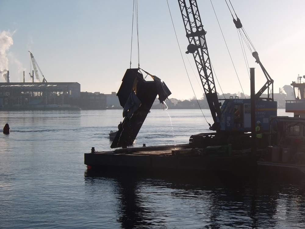 A 10,000-pound section of a fender protection system for the Memorial Bridge is lifted out of the Piscataqua River on Saturday. The panel was torn off when struck by a tanker on Friday. It was floated to the surface with airbags.