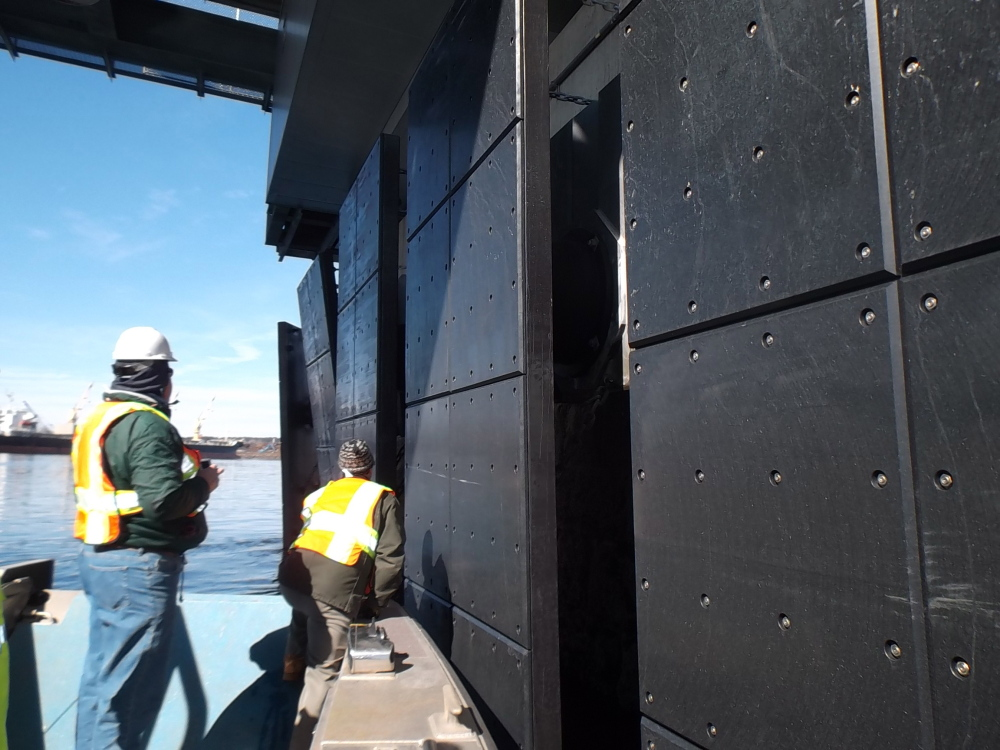 Engineers from the New Hampshire Department of Transportation get a close-up look at the damaged fender system that protects one of the piers on the Memorial Bridge. The system did its job when it was struck by a large tanker last Friday.