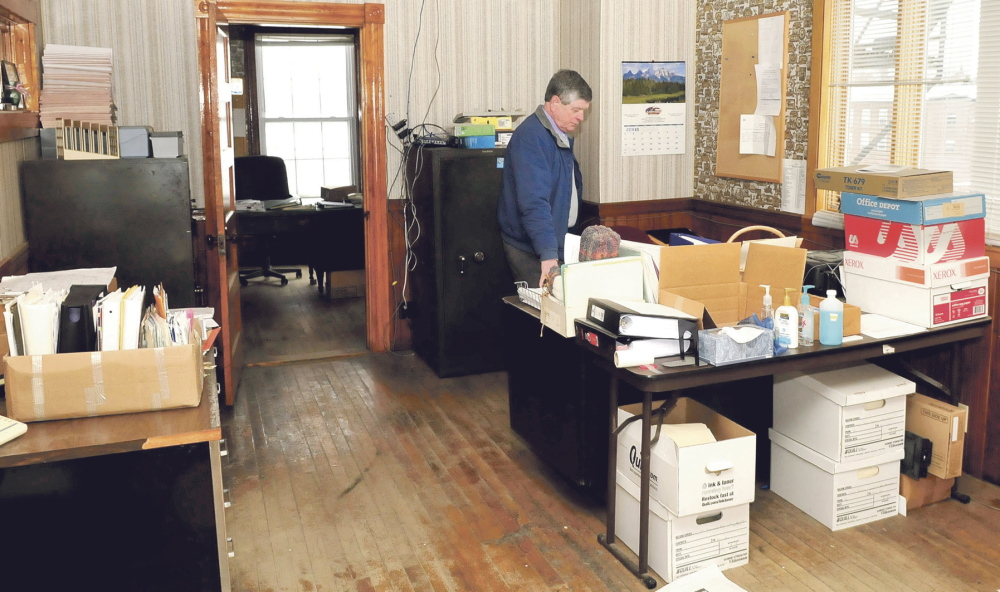 DILEMMA: Robert Worthley, Anson's administrative assistant, looks over office materials Tuesday inside the Town Office building, which has been closed because of mold, rodent infestation and sewer gas problems. Later Tuesday, a meeting was held to discuss options for a new office building after voters at town meeting rejected money to fix the old one.