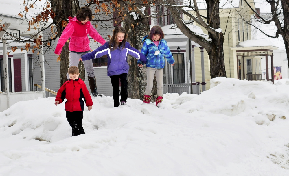 RISING BANKS: Children try to stay on top of tall snowbanks Tuesday in Bingham. From left are Peyton Plourde, front, Logan McDonald, Jordan Plourde and Lucy McDonald. More than a foot of new snow is expected in the area by Thursday.