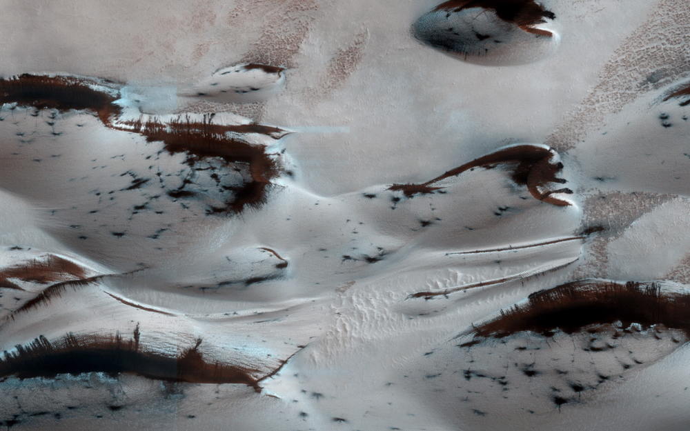FOURTH ROCK FROM THE SUN: Mars' northernmost sand dunes begin to emerge from their winter cover of carbon dioxide ice in this image taken by the Mars Reconnaissance Orbiter on Jan. 16. Dark, bare, south-facing slopes are soaking up the warmth of the climbing sun.
