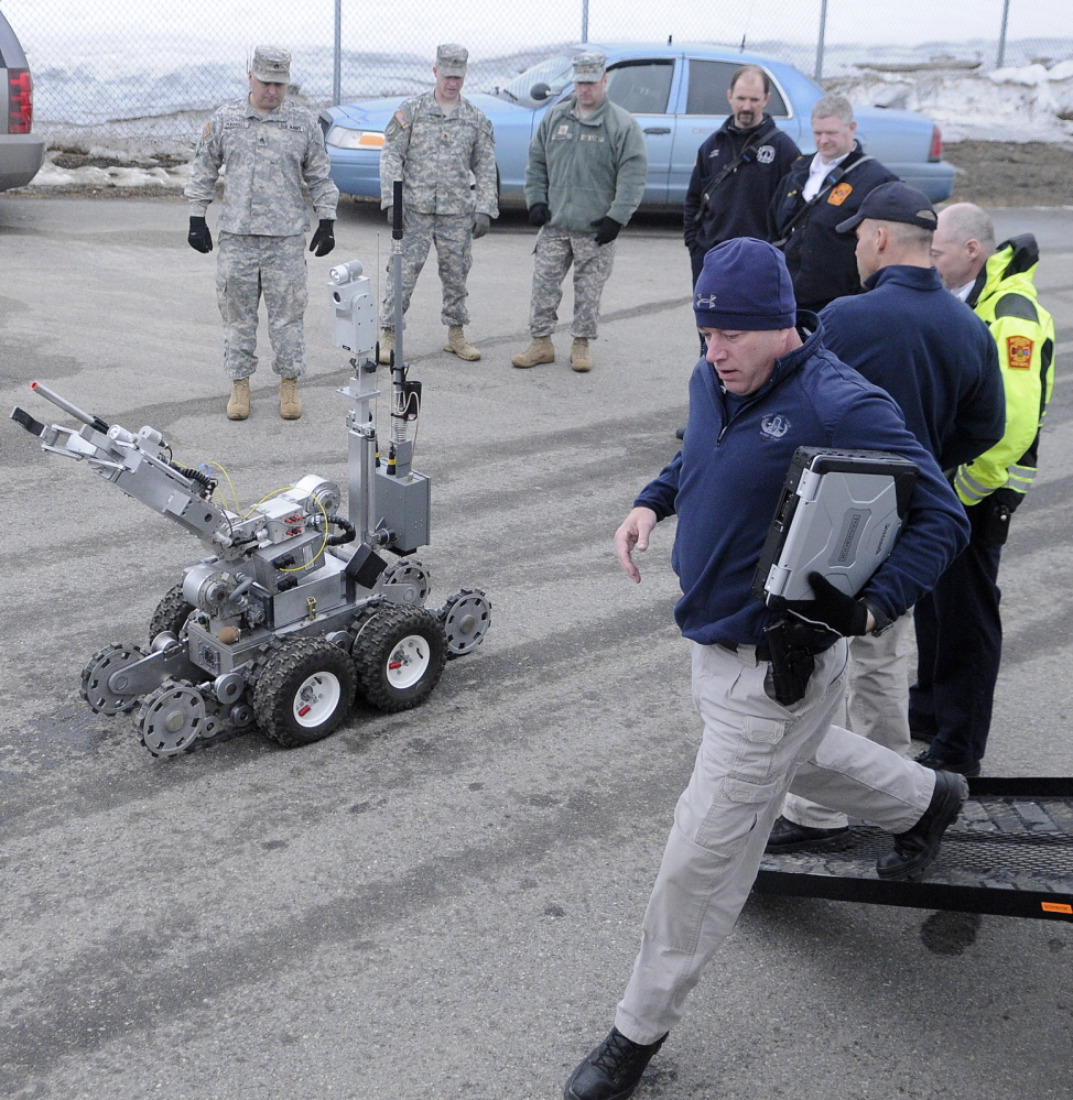 "BLAST STOPPER: State Trooper Shawn Whalen, right, runs to operate a robot Wednesday to search for a bomb at Camp Keyes in Augusta during a drill with state, local and federal emergency agencies at the state headquarters of the Army National Guard. The State Police Bombs/Explosives Unit de-activated a ""weapon"" behind the Augusta State Airport during the training."