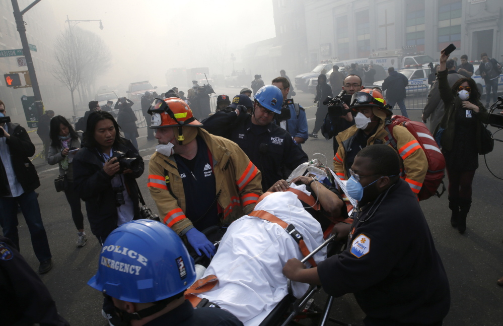 A victim is evacuated by emergency personnel near a building explosion in the Harlem section of New York City on Wednesday.