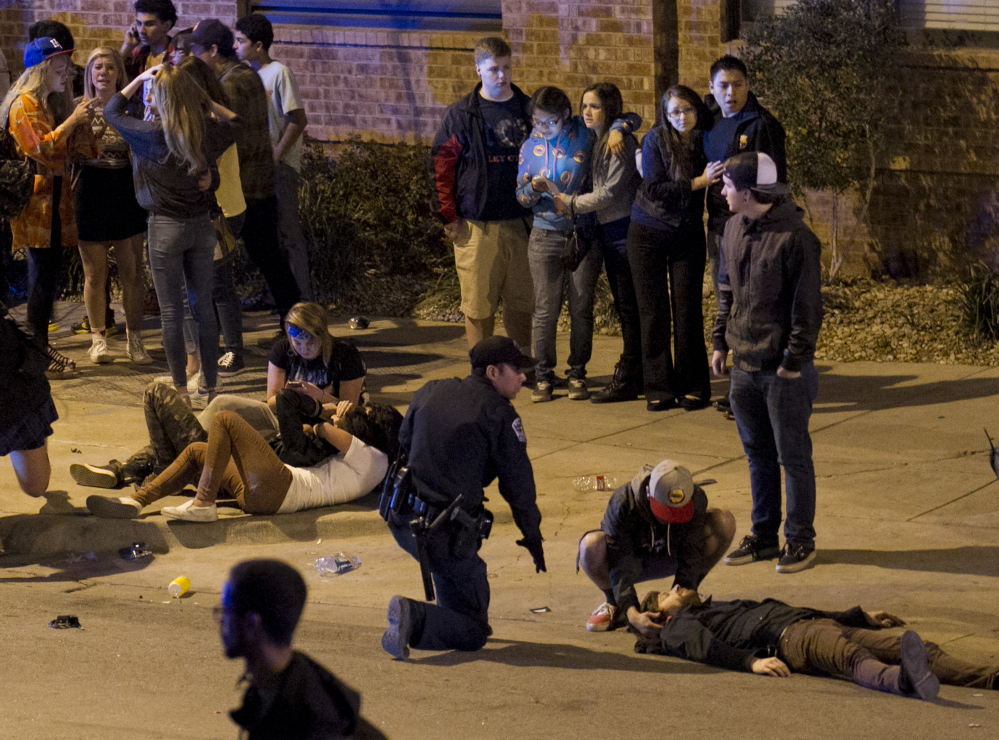 A bystander and a police officer tend to a man who was struck by a vehicle in downtown Austin, Texas.