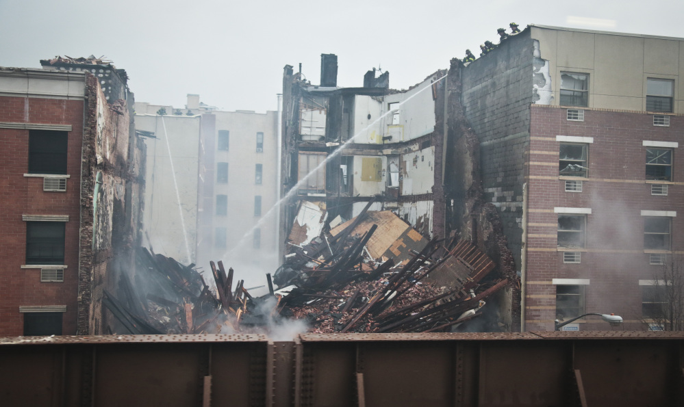Firefighters spray water on the smoldering debris from an explosion in Harlem Wednesday in New York. A gas leak triggered the explosion that shattered windows a block away, rained debris onto elevated commuter railroad tracks close by, cast a plume of smoke over the skyline and sent people running into the streets.
