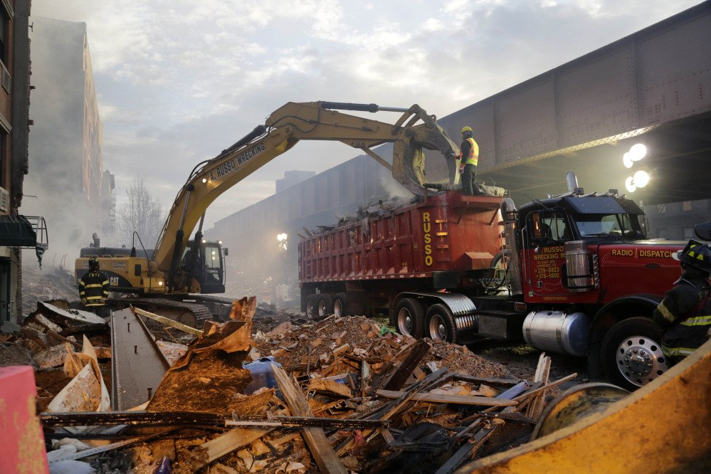 An excavator removes smashed bricks, splinters and mangled metal from the explosion site Thursday.