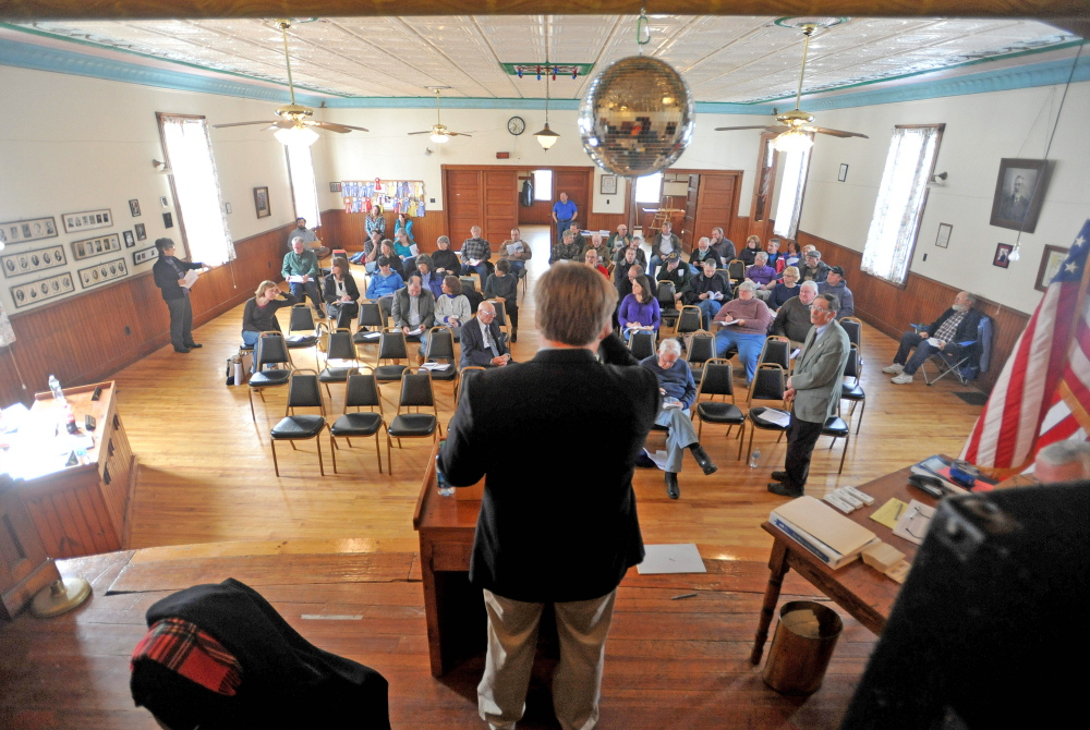 Town business: Dave Brenier, standing in the foreground, moderates the Town Meeting on Saturday at the Benton Grange.