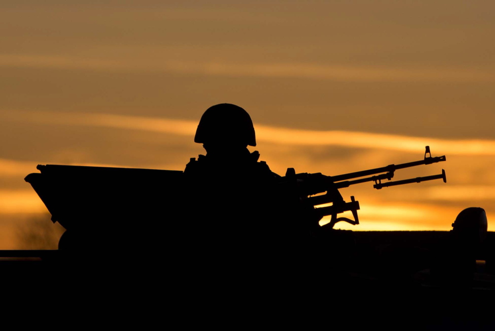 A pro-Russian soldier is silhouetted by the sunset sky as he mans a machine gun outside a Ukrainian military base in Perevalne, Ukraine, on Saturday. Tensions are high in the Black Sea peninsula of Crimea, where a referendum is to be held Sunday on whether to split off from Ukraine and seek annexation by Russia.