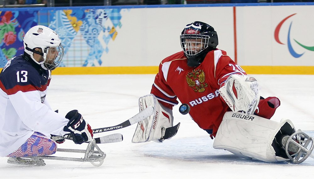 United States' Joshua Sweeney, left, shoots on goal as Russia's Vladimir Kamantcev, right, tries to defend during the gold medal ice sledge hockey game Saturday at the 2014 Winter Paralympics in Sochi, Russia. The U.S. won, 1-0.