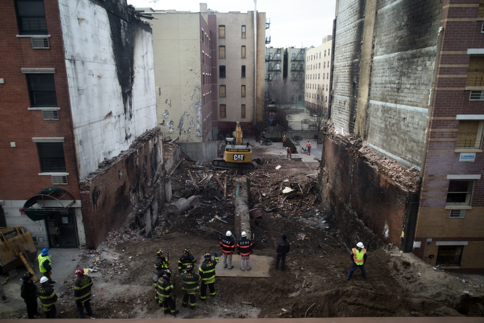 Workers stand beside the recently cleared basement of the two buildings leveled by an explosion on Wednesday in the East Harlem neighborhood of New York, Sunday.