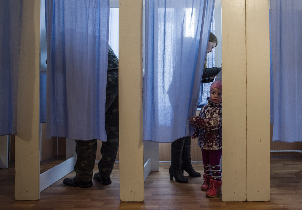A young girl peeks out of a voting booth at a polling station during the Crimean referendum in Orlinoe, near Sevastopol, Ukraine, on Sunday.