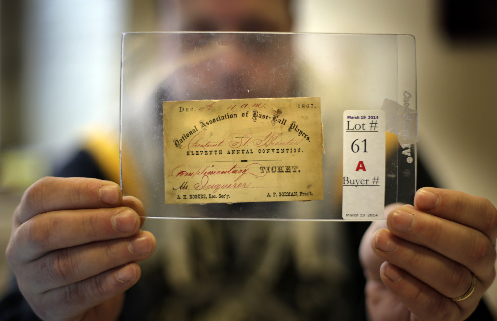 """Troy Thibodeau holds an 1870 Philadelphia Athletics season ticket. """"This old stuff is the roots of the modern game we see today. People just love it. They love history,"""" he said."""