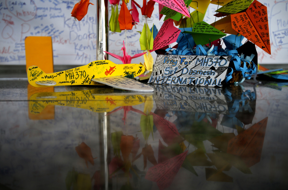 A foam plane with messages and other cards with personalized messages dedicated to people involved with the missing Malaysia Airlines jetliner MH370, is placed at the viewing gallery at Kuala Lumpur International Airport on Saturday in Sepang, Malaysia.