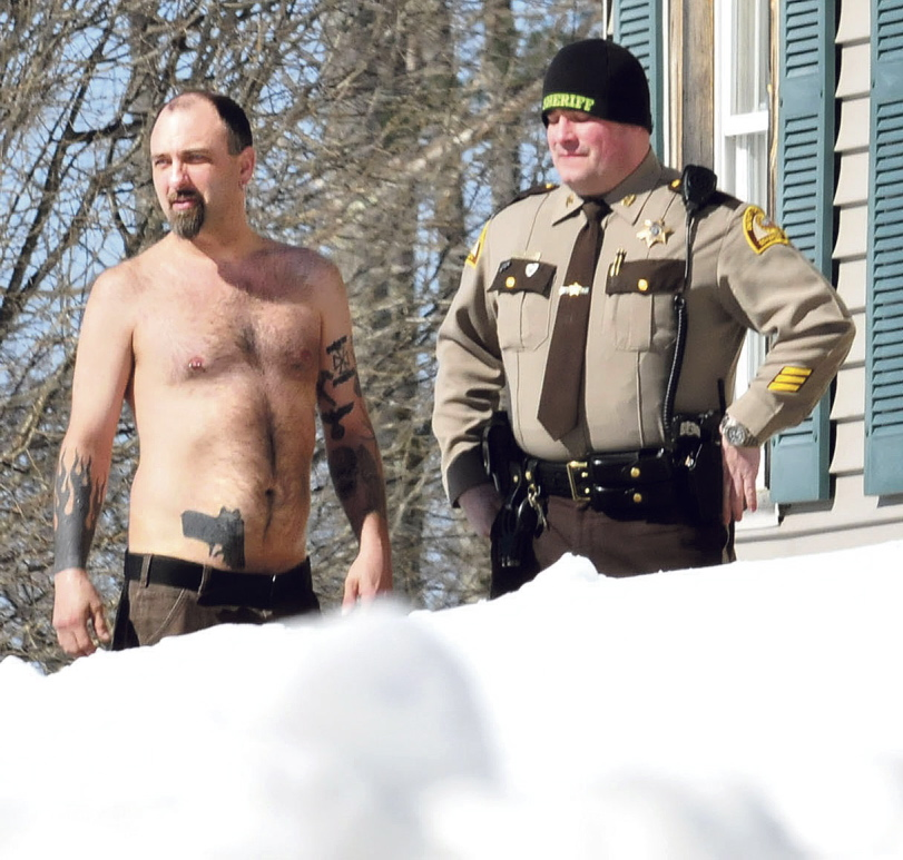 Staff photo by David LeamingCLOSE CALL: Norridgewock resident Michael Smith stands beside a Somerset County sheriff's deputy Tuesday morning. The tattoo of a pistol on his stomach was mistaken for a real firearm by employees of Lucas Tree Experts after, according to Smith, workers woke him up while they were cutting wood for Central Maine Power Co. The workers called police.