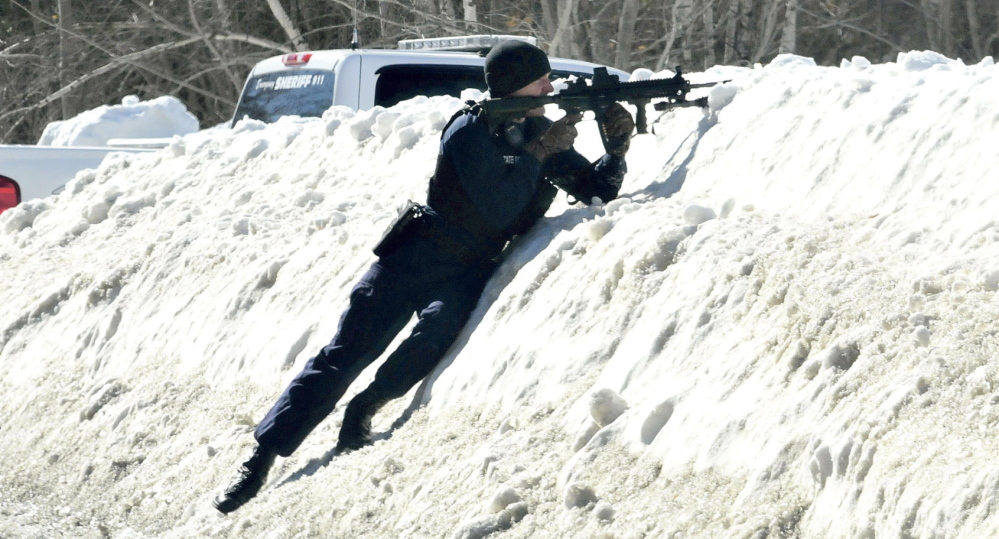 Staff photo by David LeamingARMED: Trooper Scott Duff points his rifle toward the home of Michael Smith on Tuesday morning as other police call for Smith to come out of the home in Norridgewock. Tree workers called police earlier after they mistook a pistol tattoo on Smith's stomach for a real firearm.