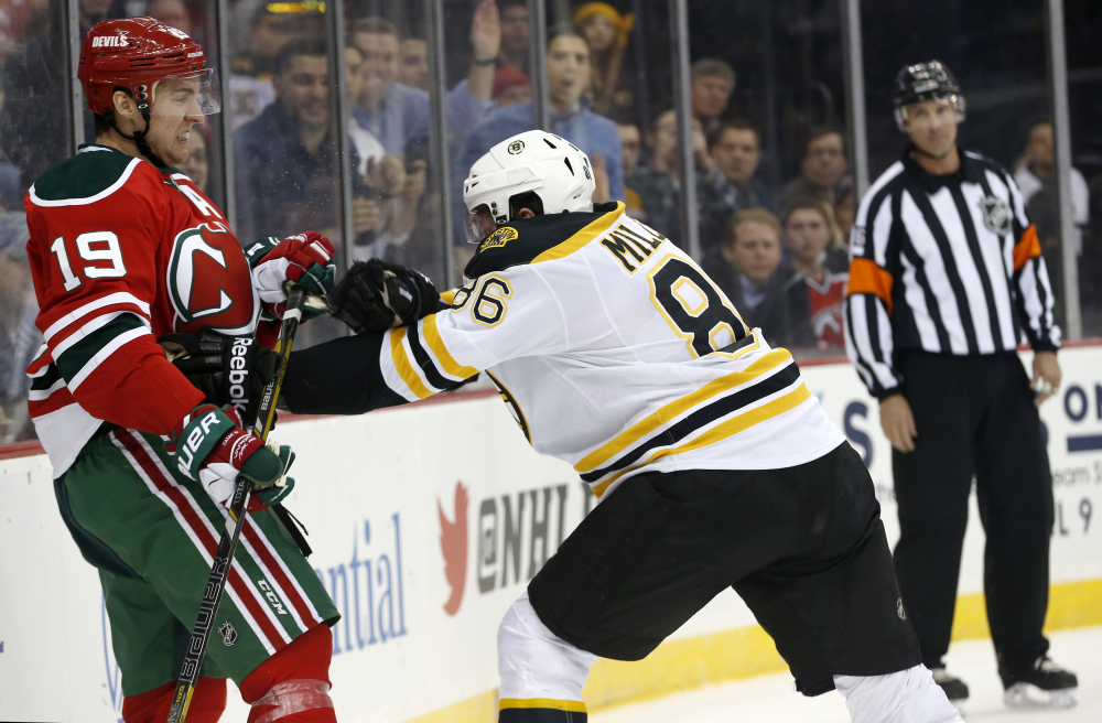 New Jersey Devils center Travis Zajac (19) is pushed by Boston Bruins defenseman Kevan Miller (86) during the second period of an NHL hockey game, Tuesday, March 18, 2014, in Newark, N.J.
