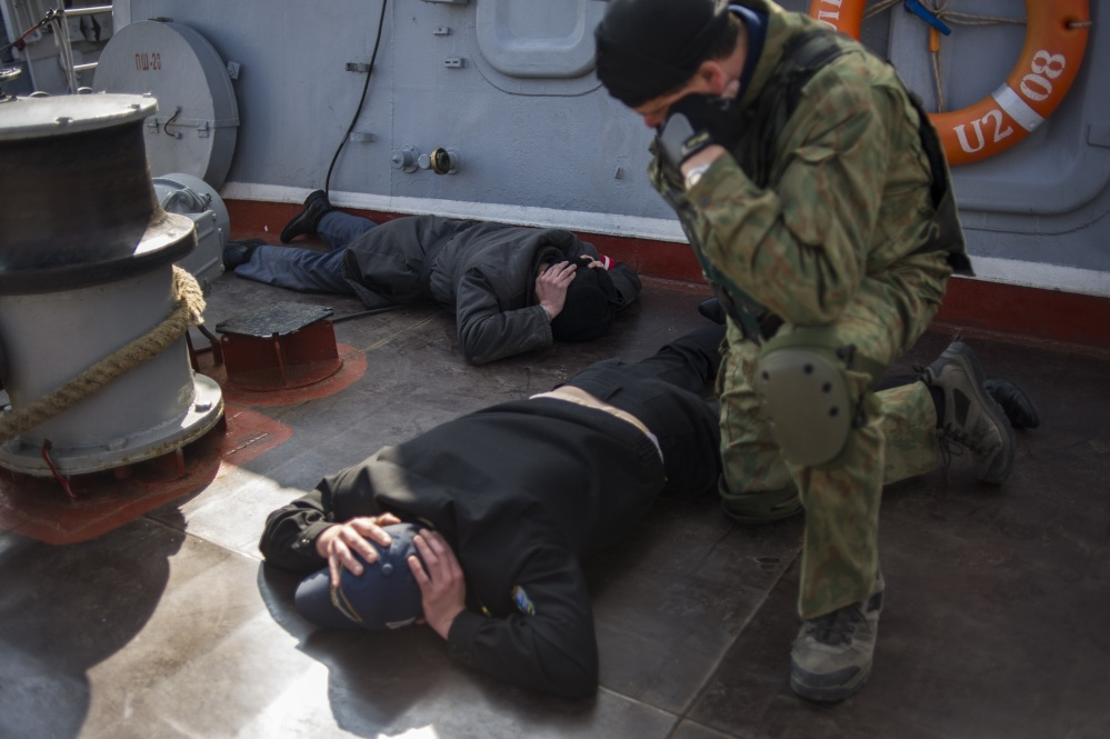 A man in an unmarked uniform, right, looks at Ukrainian crew members of the Ukrainian corvette Khmelnitsky as it was seized in Sevastopol, Crimea, Thursday.