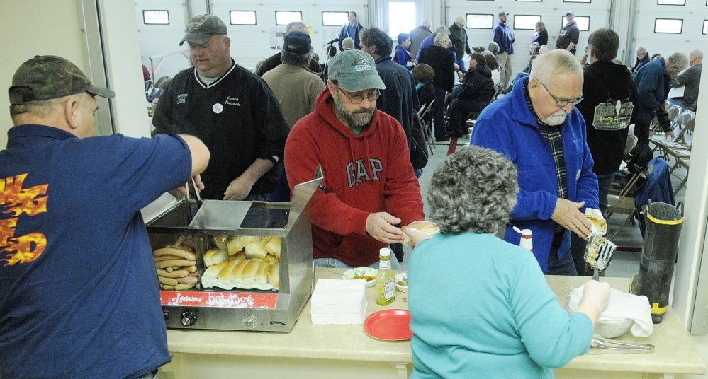 Light Lunch: Ernie Pierce, left, and Joan Mank, serve up hot dogs before the start of the 163rd West Gardiner Town Meeting on Saturday at the West Gardiner Fire Station. The dogs, sodas and treats were free, but there was a boot, at right, if anybody wanted to make a donation to the fire department.