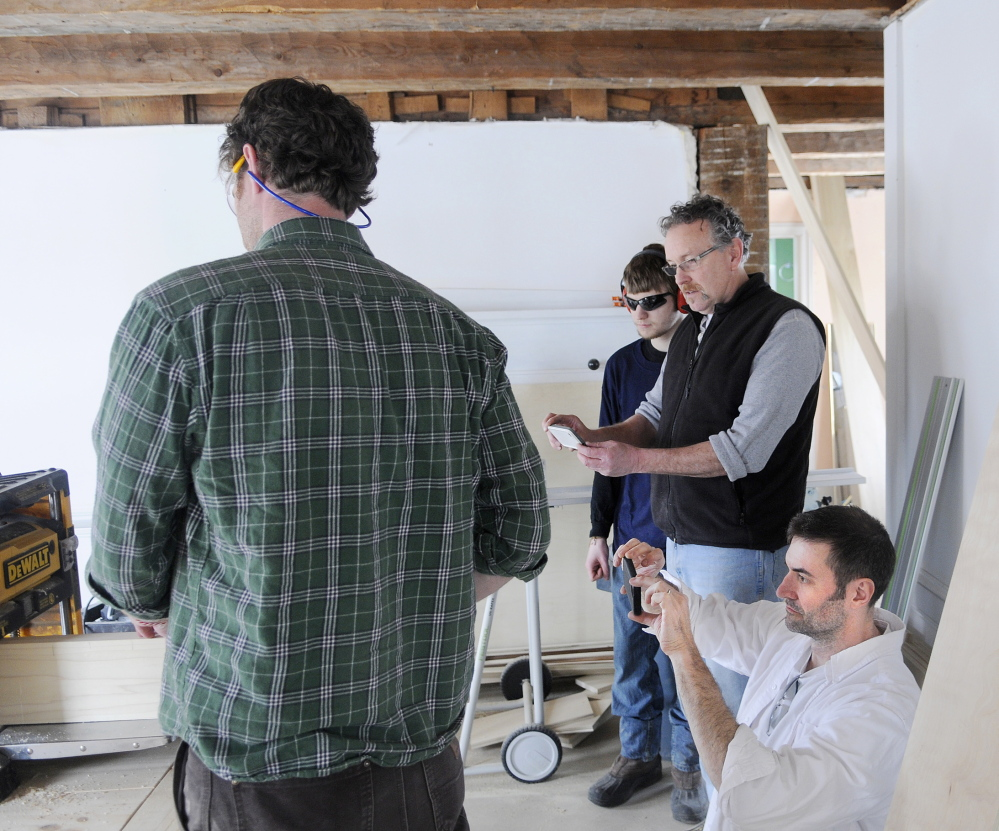 FINE HOMES: Justin Fink, left, a Fine Homebuilding magazine editor, planes a board as video producer Colin Russell, bottom right, director of photography Brian McAward and intern Matt Plourde shoot a segment at the Palermo home that builder Mike Maines is renovating.