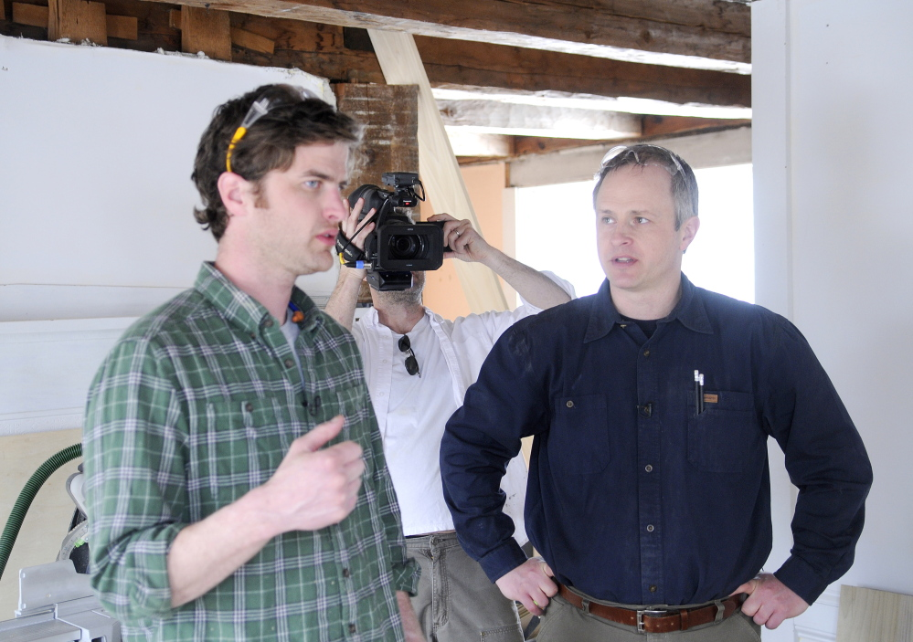 FINE HOMES: Justin Fink, left, a Fine Homebuilding magazine editor, speaks Wednesday with carpenter Mike Maines, right, as Fine Homebuilding producer Colin Russell records them at the 19th century home in Palermo that Maines is renovating. Erskine Academy senior Matt Plourde is interning with the builder and journalists.