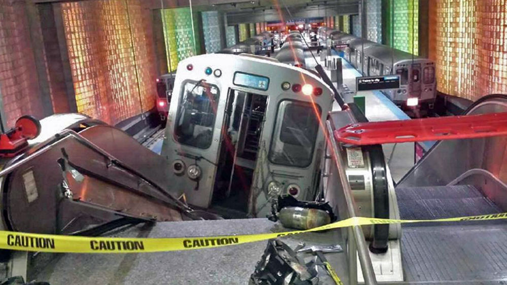 A Chicago Transit Authority train car rests on an escalator at the O'Hare Airport station after it derailed early Monday in Chicago. The train appeared to have been going too fast as it approached the end-of-the-line station and didn't stop at a bumping post – a metal shock absorber at the end of the tracks.