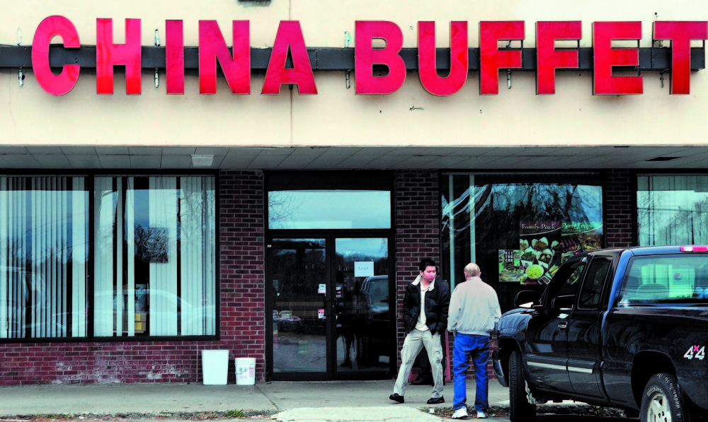 FEDERAL CHARGES: An employee, left, at the Super China Buffet restaurant on Kennedy Memorial Drive in Waterville speaks with another man shortly after U.S. Immigration and Customs Enforcement agents raided the restaurant in 2011. The former manager, Mei Juan Zhang, 31, of Fairfield, was sentenced to 14 months in prision and three years of supervised release on a number of charges related to the raid.