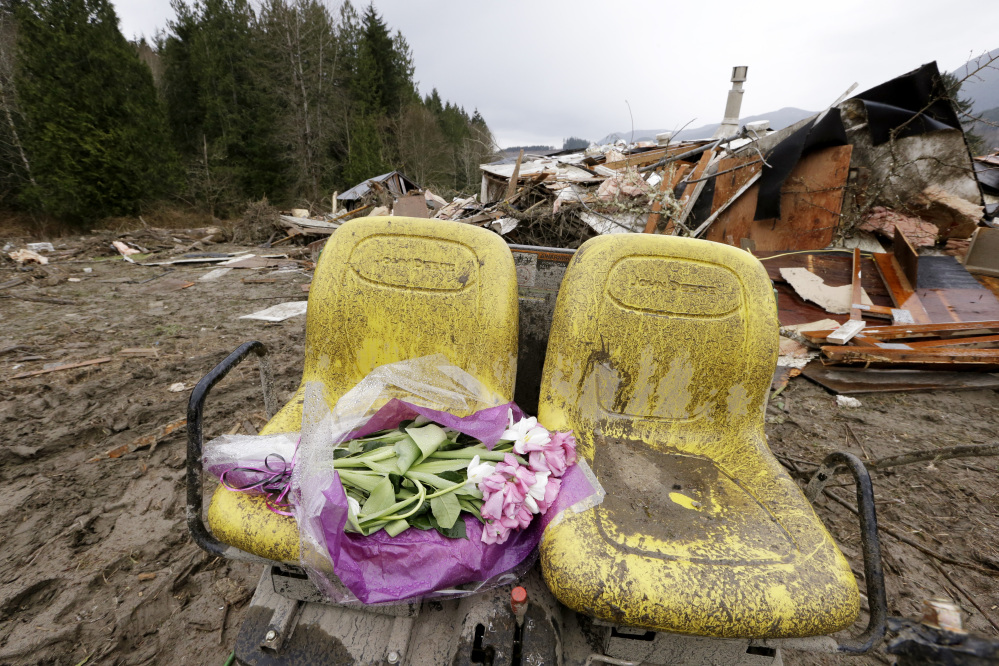 Flowers are left on debris Tuesday next to a demolished home where a woman's body was found following a deadly mudslide in Arlington, Wash. At least 14 people were killed and searchers expect to find more bodies.