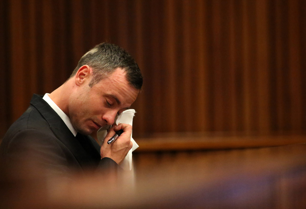 Oscar Pistorius reacts in the dock during cross questioning about mobile phone text messages between him and Reeva Steenkamp in court in Pretoria, South Africa, Tuesday.