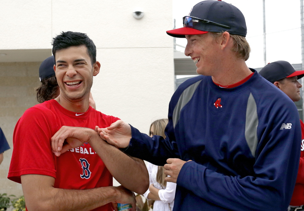 TOGETHER FOR NOW: Noe Ramirez, left, and Henry Owens, right, both pitchers in the Boston Red Sox organization, joke with each other while watching a minor league spring training game last week in Fort Myers, Fla. Ramirez and Owens are close friends, and both grew up in Southern California.