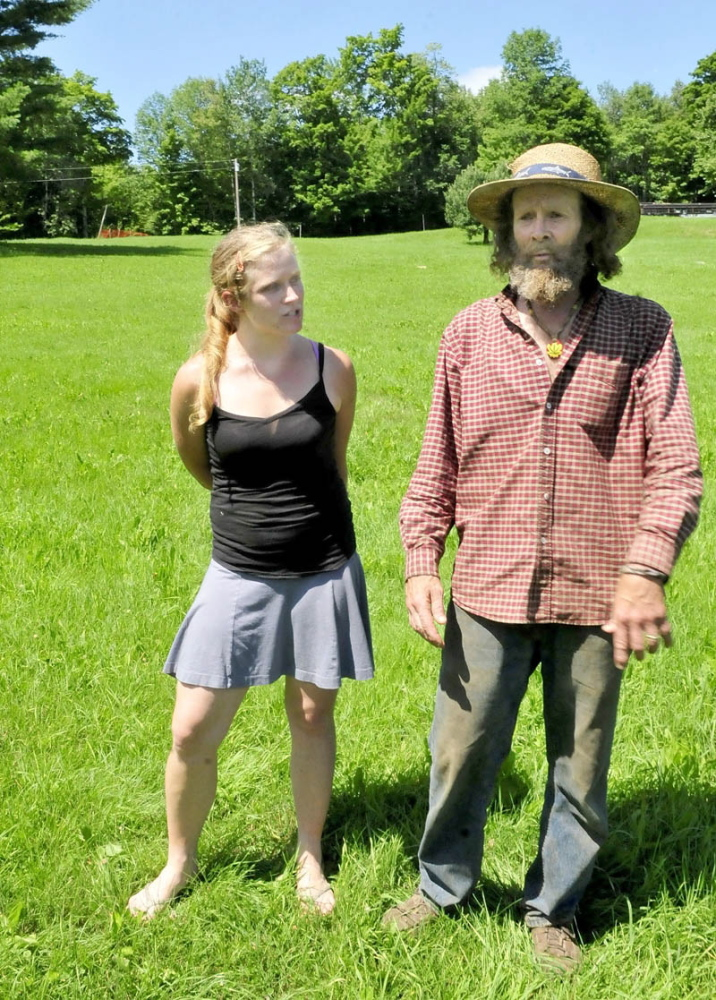 UNWELCOME DEVELOPMENT: Starks residents Elizabeth Smedberg and Harry Brown speak in July 2013 in a field off Abijah Hill Road, directly below the proposed site of a celltower. Brown and his wife, Cindy, who live near the site, have appealed in Somerset County Superior Court the town's August decision to allow the 195-foot tower.