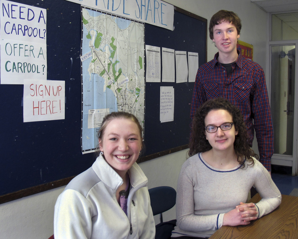 Burlington High School seniors Abby Massell, left, Sabine Rogers and Henry Prine pose in front of a map they helped create to assist students to find rides to and from school as a strike by local bus drivers continued into its second week.