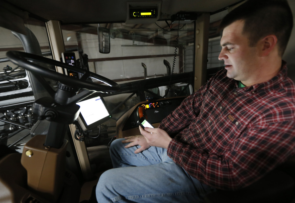 Nick Guetterman looks over the data shared by his crop sprayer and cell phone while on his farm near Bucyrus, Kan., Wednesday.