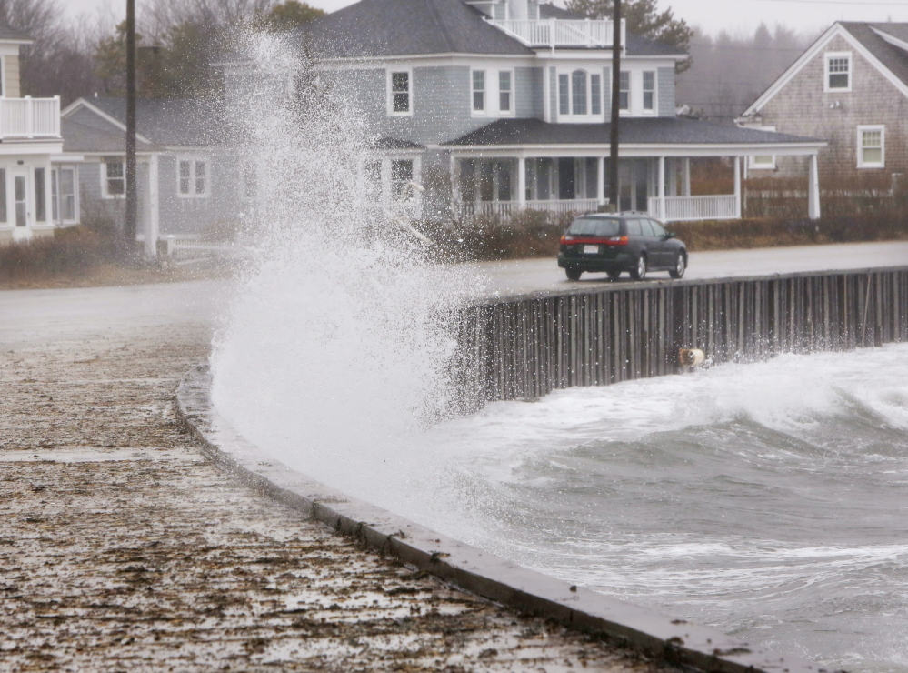 KENNEBUNK, ME - MARCH 30 A car drives along Beach Avenue in Kennebunk on Sunday, March 30, 2014 as a wave hits a seawall, spalshing water on to the sidewalk. A combination of an astronmical high tide and strong winds caused minor coastal flooding along areas of the southern Maine coast on Sunday. (Photo by Gregory Rec/Portland Press Herald)