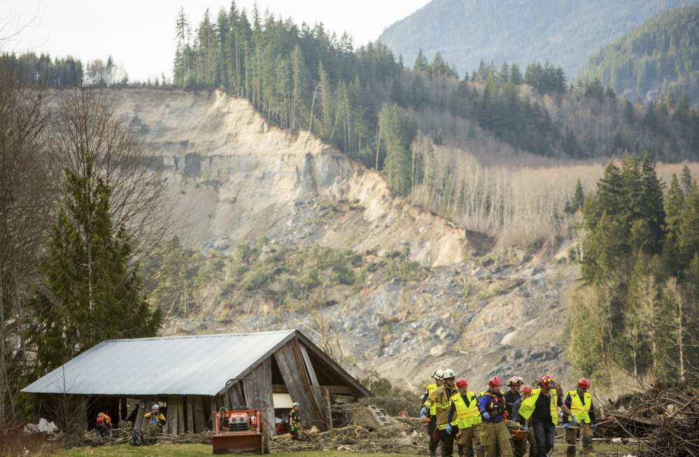 Rescue workers remove a body from the wreckage of homes that were destroyed by a mudslide near Oso, Wash., on March 24. The deadly disaster points to the need for a national inventory of areas that are vulnerable to slides.