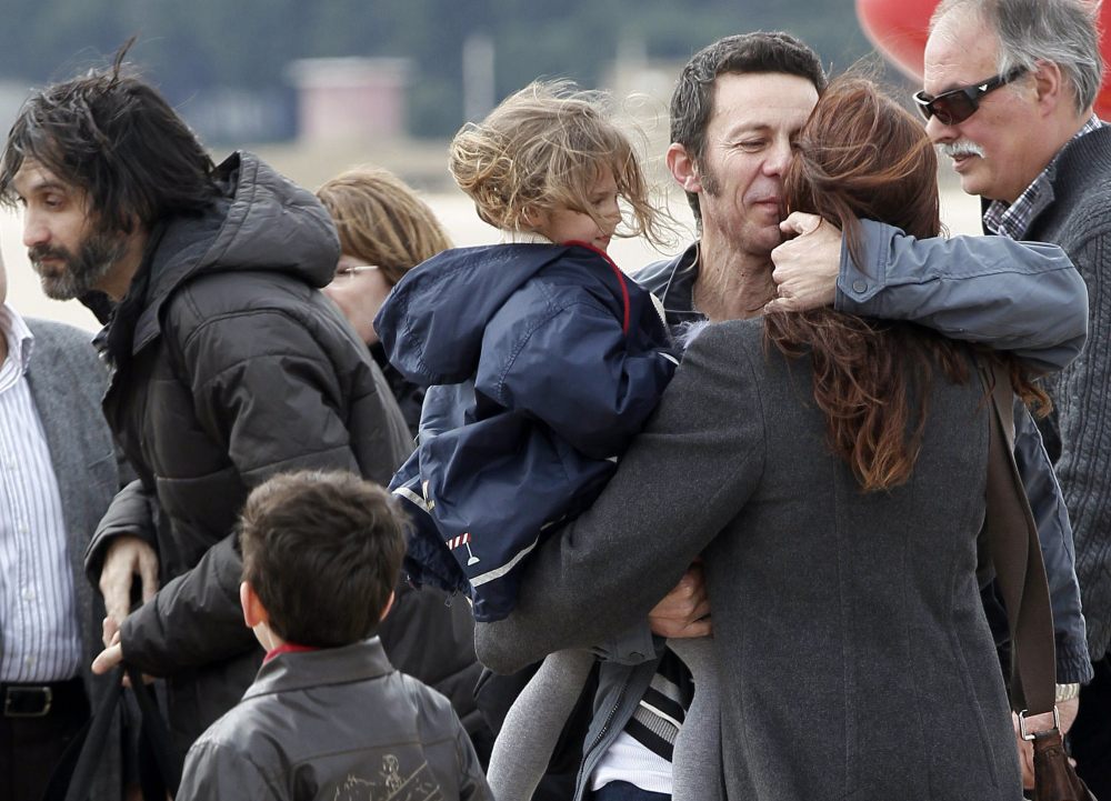 Spanish reporter Javier Espinosa, second right, holds his daughter, Nur, as he is greeted by his wife, Monica Garcia, upon his arrival at the military airport of Torrejon in Madrid, Spain, on Sunday. Espinosa and fellow journalist Ricardo Garcia Vilanova were freed after being kidnapped for more than six months in Syria by a rogue al-Qaida group.