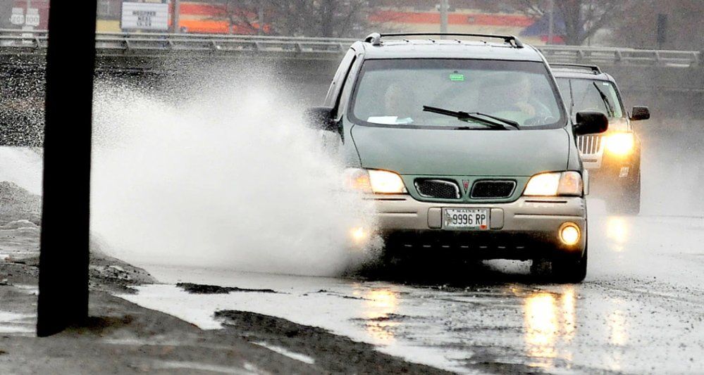 Staff photo by David Leaming SPLASH: Motorists drive through water puddles made from steady rain on Sunday, March 30, 2014, in Waterville. Parts of Franklin and Somerset counties were expected to get both rain and snow later in the day.