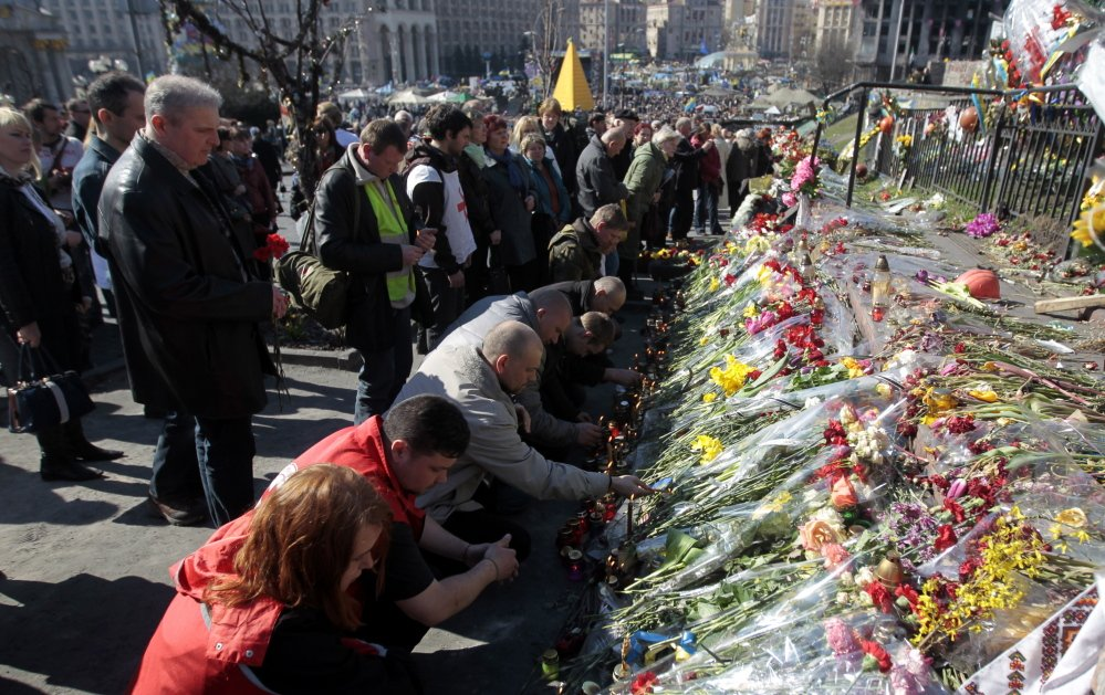 People lay flowers and lit candles at one of the barricades during a mourning rally in memory of those killed during mass protests in Kiev in Kiev's Independence Square on Sunday.