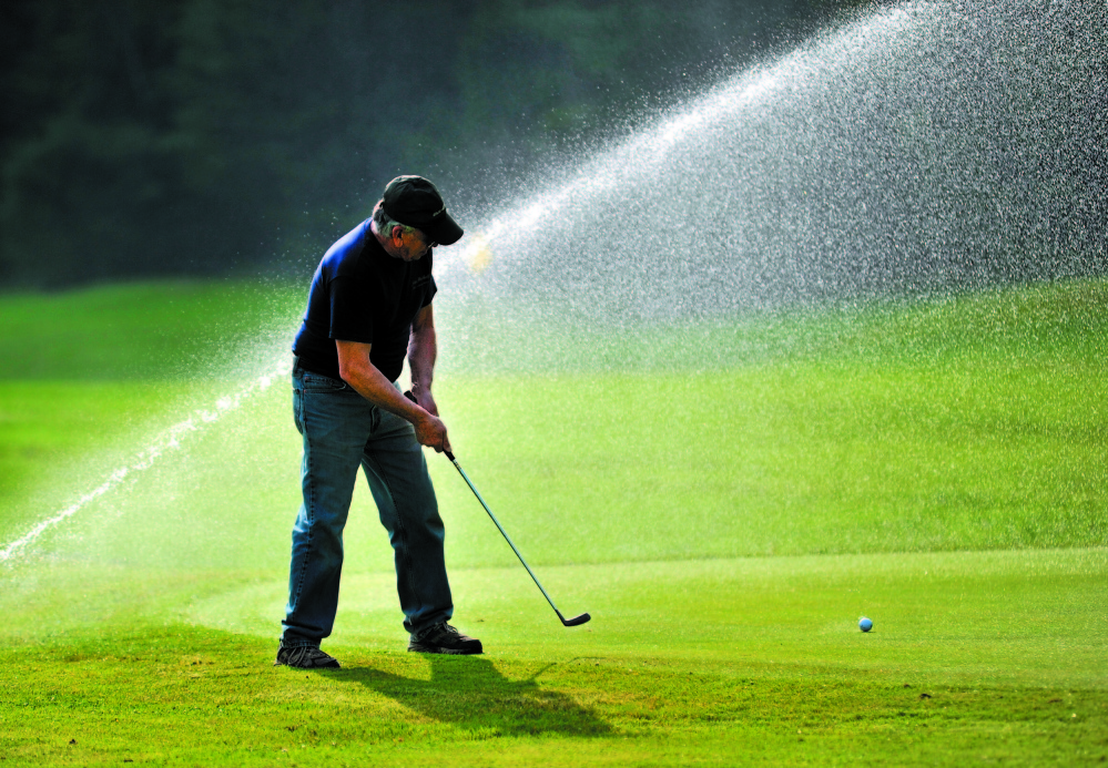 ON THE GREEN: David Bolduc concentrates on his putt on the second green as the sprinklers fire behind him at Pine Ridge Golf Course on West River Road in Waterville in this 2011 file photo.