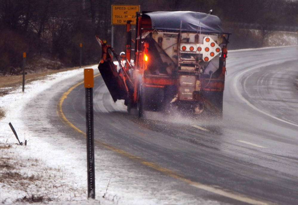 A snowplow spreads sand on the ramp from the Maine Turnpike to I-295 in Scarborough. A wintry mix caused a spate of accidents on roads throughout southern Maine on Monday morning.