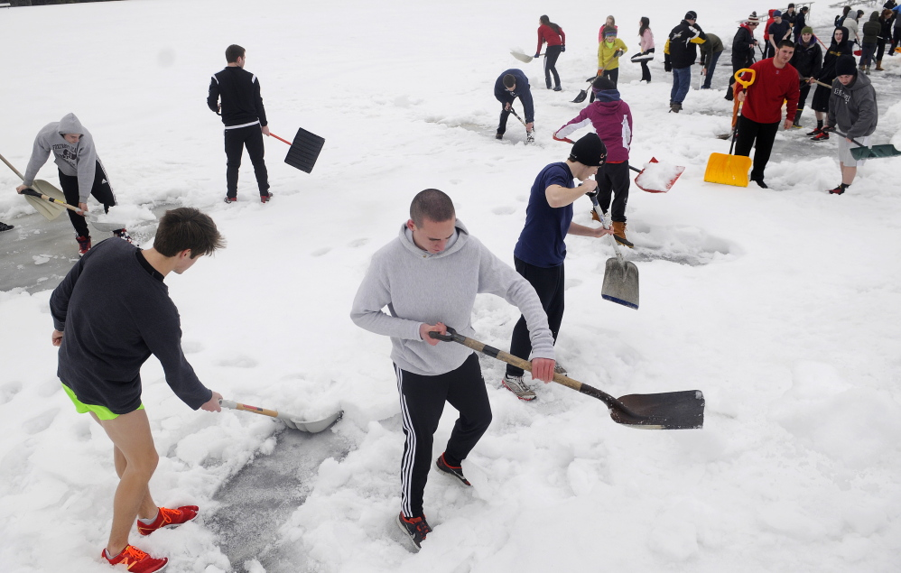 Staff photo by Andy Molloy SHOVEL READY: Hall-Dale High School track team members began practice Monday, the first day of spring sports, by clearing the track. The forty athletes removed several inches of snow from six lanes of the track for about 200 meters.
