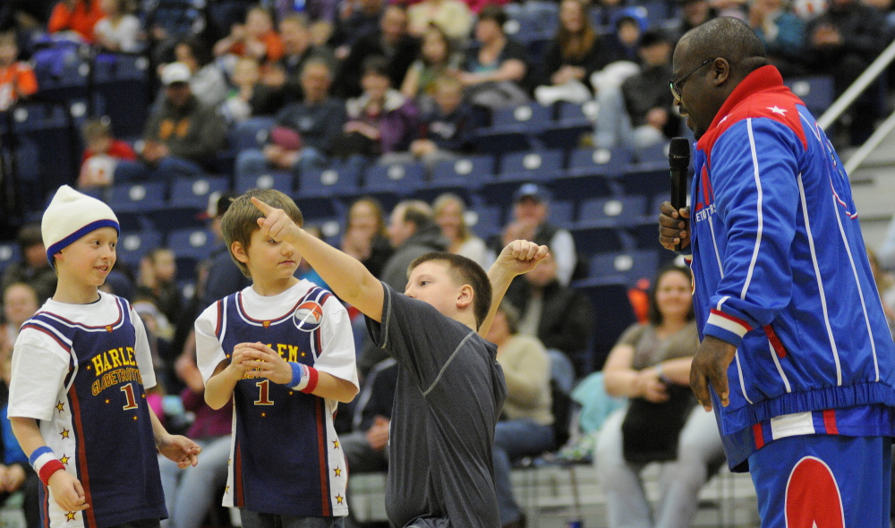 Staff photo by Andy Molloy Nathan Love, center, 10, of Belgrade throws down the love Monday night during a Harlem Globetrotters match in Augusta.