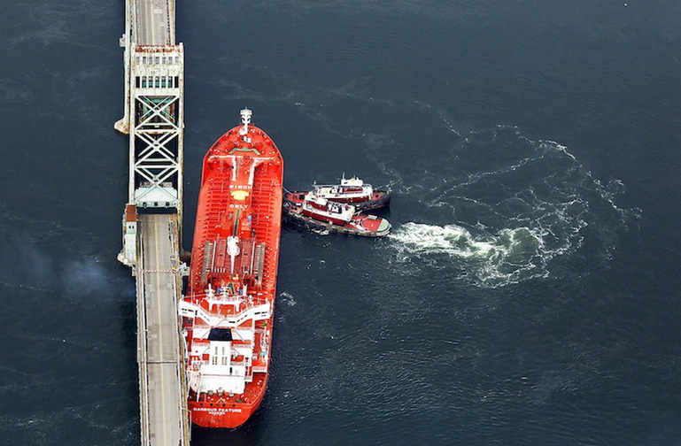 Seen in this aerial photograph, tugboats hold the MV Harbour Feature in place against the Sarah Mildred Long Bridge in Kittery on April 1, 2013, after it slipped off its moorings at the New Hampshire State Pier and crashed into the bridge.