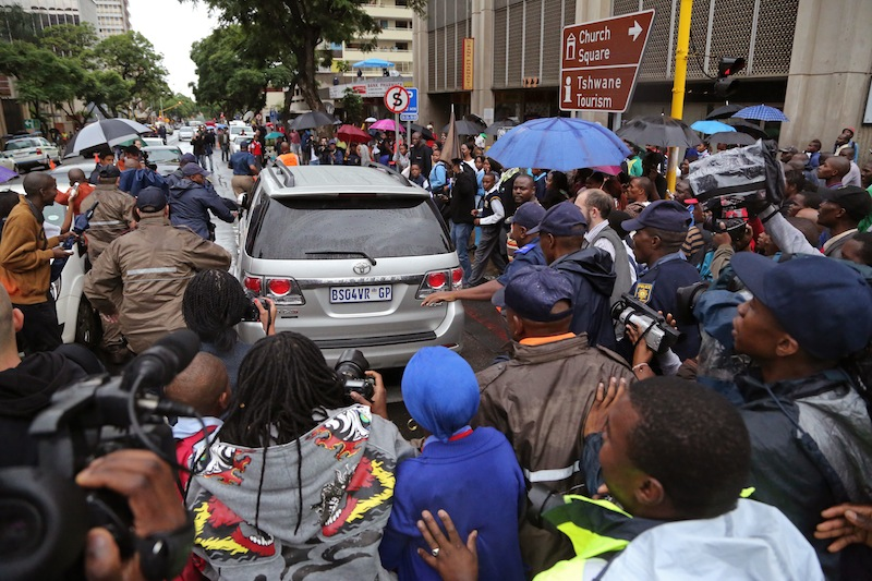 People run after the car that is transporting Oscar Pistorius from the high court after the first day of his trial in Pretoria, South Africa, Monday, March 3, 2014. Pistorius is charged with murder with premeditation in the shooting death of girlfriend Reeva Steenkamp in the pre-dawn hours of Valentine's Day 2013.